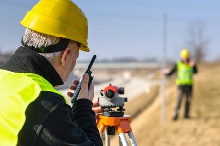 Land surveyors measuring with tacheometer speaking through transmitter highway Stock fotó