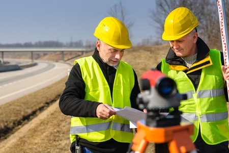 geodesist: Two male geodesist with tacheometer checking plans standing by highway