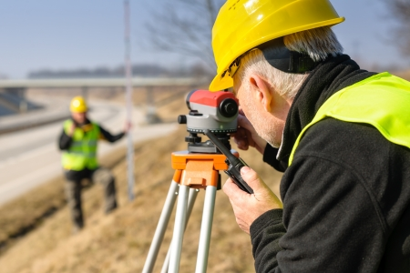 geodetic: Land surveyors on highway measuring with theodolite
