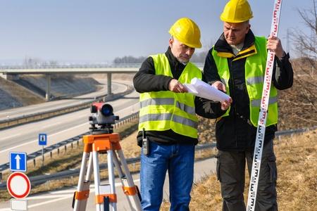 Land surveyors on highway reading geodesist plans use tacheometer photo