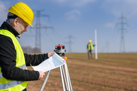 Land surveyors on construction site reading plans wear reflective clothing Stock Photo - 13318815