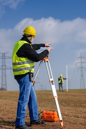 tacheometer: Land surveyors measuring with tacheometer point direction looking at plan Stock Photo