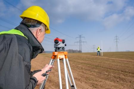 surveyors: Land surveyors measuring with tacheometer speaking through transmitter