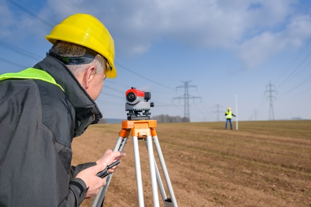 geodetic: Land surveyors measuring with tacheometer speaking through transmitter
