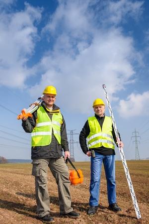 Portrait de deux appareils de mesure géodésien tenant sur le site de construction