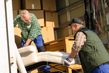 Deux hommes déménageurs mettre meubles et les boîtes de camion de déménagement Banque d'images