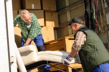carga: Dos motores masculinos poner muebles y cajas en el movimiento de camiones