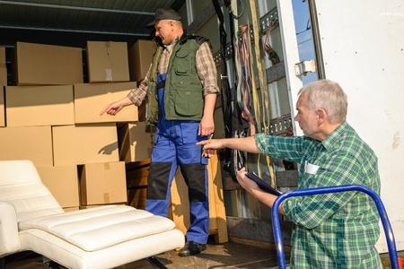 carga: Dos motores hombres descargan muebles y cajas de camioneta en movimiento Foto de archivo