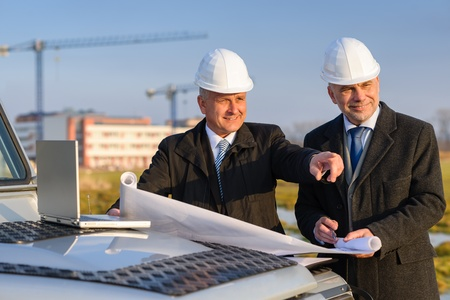 Male developers with blueprints at  construction site discuss architect project Stock Photo - 13321400