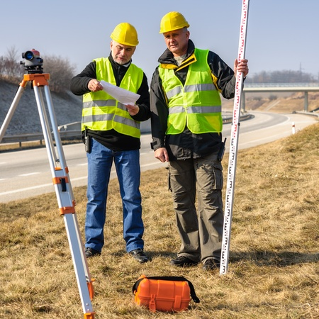 surveyor: Two male geodesist with tacheometer checking plans standing by highway