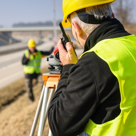 Land surveyors on highway measuring with theodolite photo
