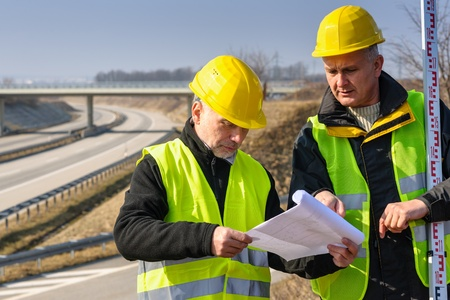 geodetic: Land surveyors on highway reading geodesist plans use tacheometer