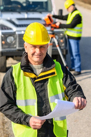 protective clothing: Male geodesist in reflective vest and helmet hold land plans