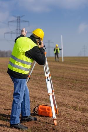 tacheometer: Land surveyors measuring land with theodolite speaking through transmitter Stock Photo