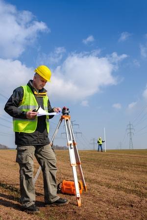 teodolito: Los agrimensores de medición con taquímetro buscando en el sitio de plan de construcción