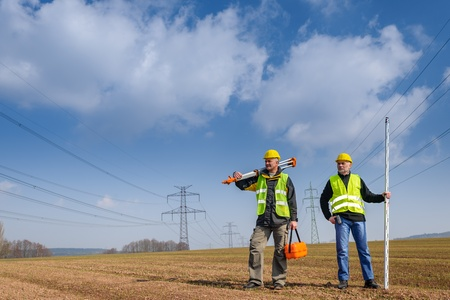 teodolito: Retrato de dos equipos de medición geodesta la celebración en el sitio de construcción