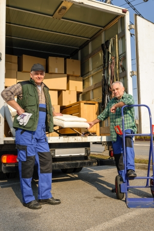 loading truck: Two male movers unload furniture and boxes  from moving truck