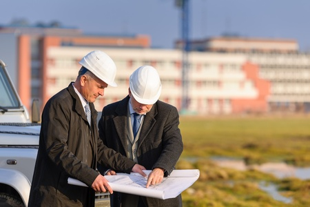developers: Two senior architect developers review plans at a construction site Stock Photo