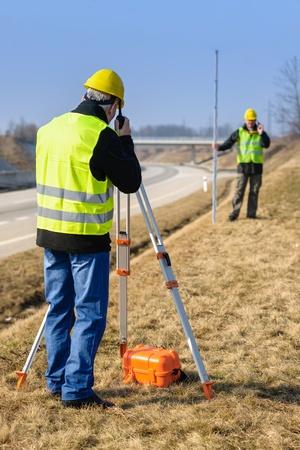 geodesist: Land surveyors measuring with tacheometer speaking through transmitter highway Stock Photo