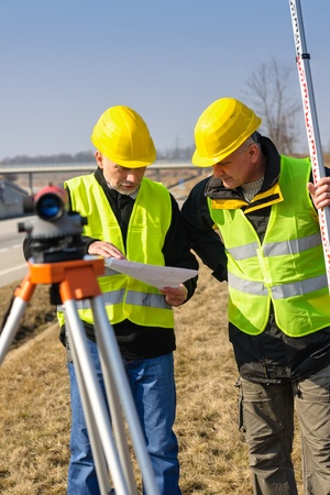 tacheometer: Two male geodesist with tacheometer checking plans standing by highway