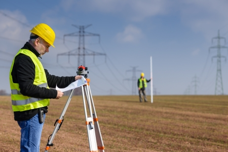 Land surveyors on construction site reading plans wear reflective clothing photo