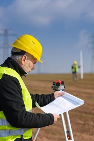 tacheometer: Land surveyors on construction site reading plans measure tacheometer