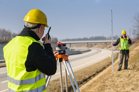 geodetic: Land surveyors measuring with tacheometer speaking through transmitter highway Stock Photo