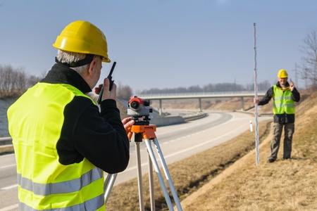 teodolito: Los agrimensores de medición con taquímetro hablando a través de la autopista del transmisor