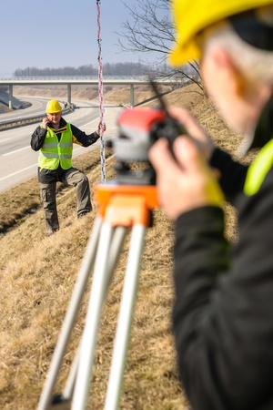 geodesist: Land surveyors on highway measuring with theodolite