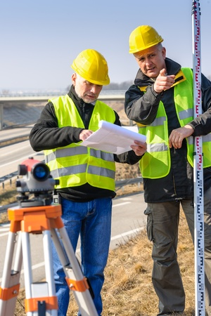surveyors: Land surveyors on highway reading geodesist plans use tacheometer