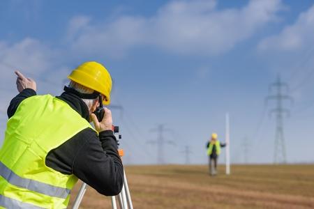 Land surveyors measuring with tacheometer speaking through transmitter construction site