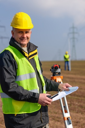 tacheometer: Land surveyors measuring with tacheometer hold construction plans on site