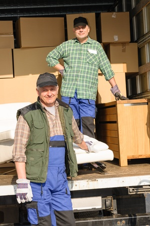 moving van: Two movers man loading furniture and boxes from truck vehicle