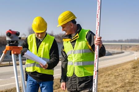 teodolito: Dos hombres geodesta con la comprobación de los planes de taquímetro de pie junto a la carretera