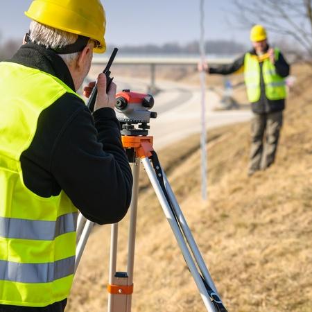 teodolito: Los agrimensores en la carretera de medición con teodolito