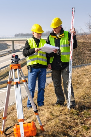 geodesist: Land surveyors on highway reading geodesist plans use tacheometer