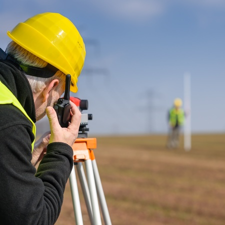 tacheometer: Land surveyors measuring land with tacheometer speaking through transmitter Stock Photo