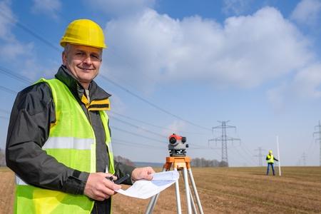 geodesist: Land surveyors measuring with tacheometer wear reflective safety vest