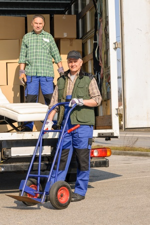 Two movers man loading furniture and boxes from truck vehicle photo