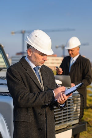 developers: Male architect developers on construction site making notes building project