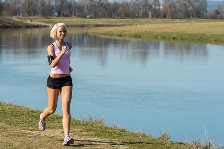 Young woman jogging recreational running by river sunny day photo
