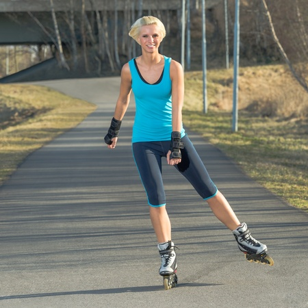inline skater: Happy woman roller skating sport smiling in park sunny day Stock Photo