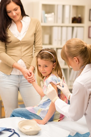 Little girl getting vaccination from pediatrician at office photo