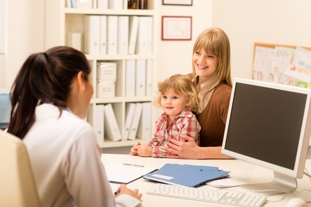 Young woman with little daughter having consultation at pediatrician office photo