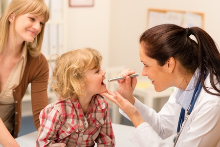 patient: Little girl having throat examination by pediatrician using light pen Stock Photo