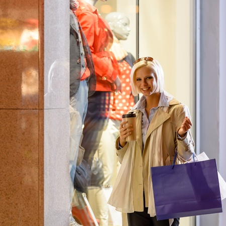 lifestyle shopping: Woman stand by shop window with bags drink coffee night