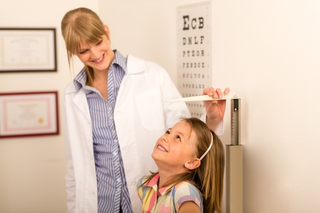 measure height: Pediatrician measure height of little girl at medical office