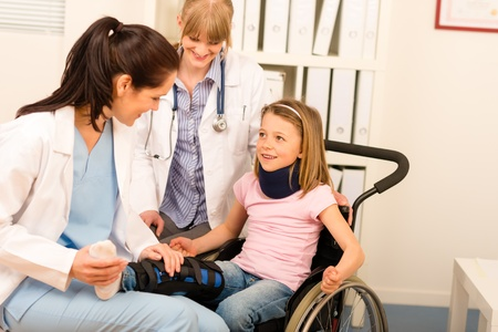 Little injured girl on wheelchair with doctors at medical office photo