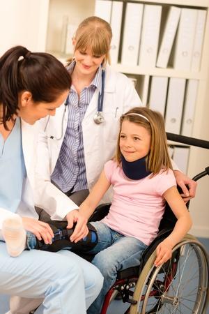 pierna rota: Niña herida en la silla de ruedas con los médicos del consultorio médico