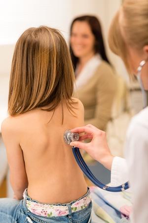 Chica que se examinará con el estetoscopio por el pediatra en el consultorio médico